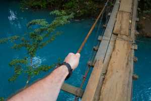 A tourist walks over a rickety bridge that crosses the milky blue water of the Rio Celeste - Costa Rica-Cosmic Travel