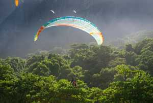 Paraglider passes along the misty greenery of Tijuca National Forest at São Conrado. - Brésil-Cosmic Travel
