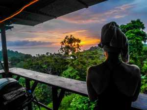 Woman with a towel on her head after the shower standing and watching sunset. - Costa Rica-Cosmic Travel